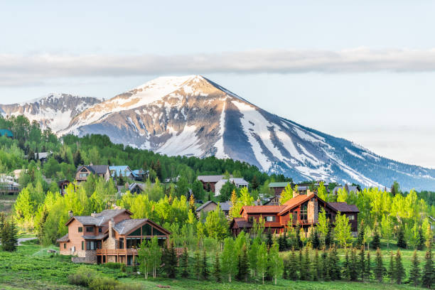 Mount Crested Butte, Colorado village in summer with colorful sunrise by wooden lodging houses on hills with green trees stock photo
