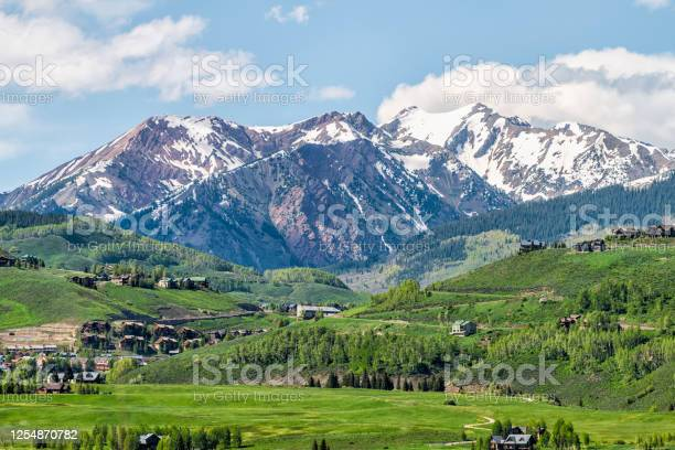 Photo of Mount Crested Butte mountain peak range and village in summer with lodging houses on hills with green grass open hill and snowcapped rocky mountains