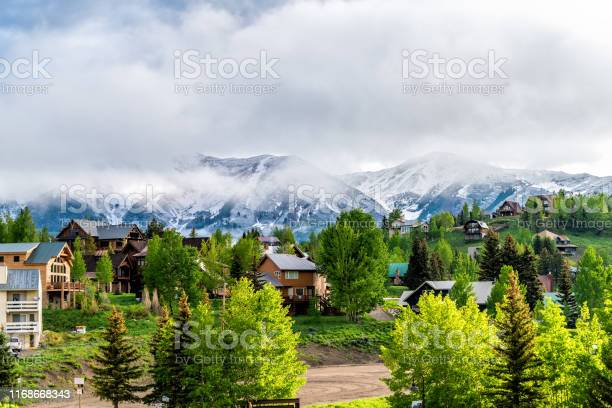 Photo of Mount Crested Butte, USA Colorado village in summer with cloudy fog mist sunrise morning and houses on hills with green trees