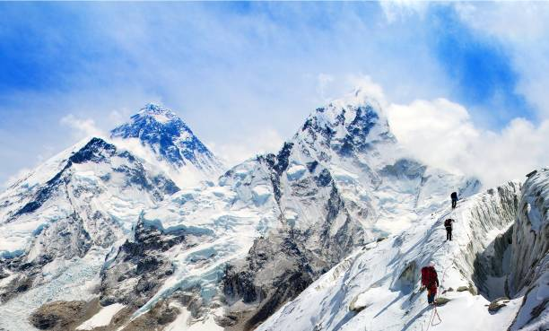 mount everest from kala patthar with group of climbers - clambering stock photos and pictures