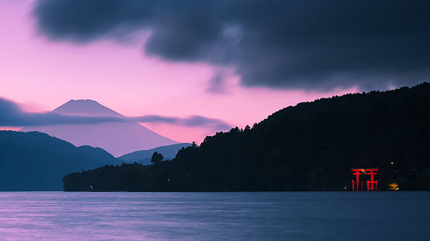 Mount Fuji and Torii Gate A torii gate is lit up on the shoreline, while a pink and purple sun sets over Mount Fuji in the backdrop. shrine stock pictures, royalty-free photos & images