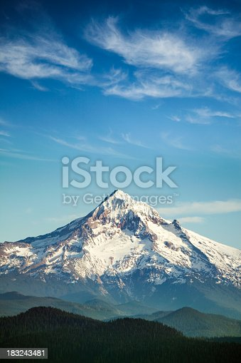 A scenic view of Mt. Hood, and the surrounding hills, a gorgeous cloudscape and blue sky overhead.  One of the many beautiful mountains in the Pacific Northwest.  Vertical with copy space.