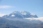 An extinct volcano Illimani sits on a hazy blue sky day near La Paz, Bolivia