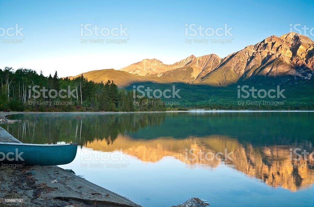 Mount Pyramid and lake with canoe. stock photo