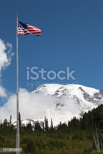 Mount Rainier and the American Flag in the front on a sunny day; vulcano 4392 meter high