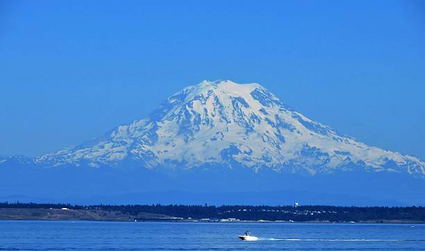 Mount Rainier with Boat Racing Across the Puget Sound Mount Rainier Watches As Speed Boat Races across the Puget Sound gig harbor stock pictures, royalty-free photos & images