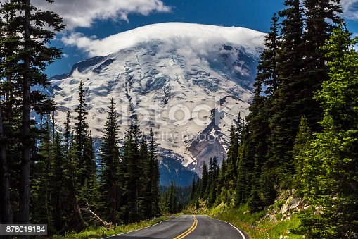 Steep Mountain Road with Stunning View of Cloud Topped Mount Rainier in August.  Unusual umbrella cloud (lenticular) formation on top.