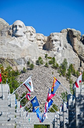 The four presidents of Mount Rushmore stare in various directions - George Washington, Thomas Jefferson, Theodore Roosevelt and Abraham Lincoln.  The National Memorial was created by over 400 workers carving, blasting and chiseling the honeycomb granite of the Black Hills between 1927 and 1941.  Pictured here is the Avenue of Flags, leading up to the memorial overview.  Each state is represented here with their state flag.