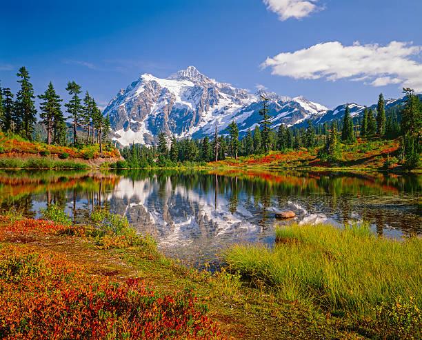Monte Shuksan, foto do lago, a montanha com os cumes gelados, escovas com cores de outono - foto de acervo