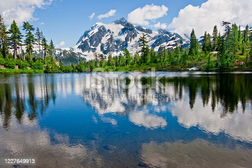 The North Cascades is a vast wilderness of conifer-clad mountains, glaciers and lakes.  It is one of the more remote wilderness areas in the Continental United States.  Because of its striking beauty, Mount Shuksan in the North Cascades, is one of the most photographed mountains in the world.   This picture of Mount Shuksan reflected in the water was taken from Picture Lake in the Mount Baker National Forest in Washington State, USA.