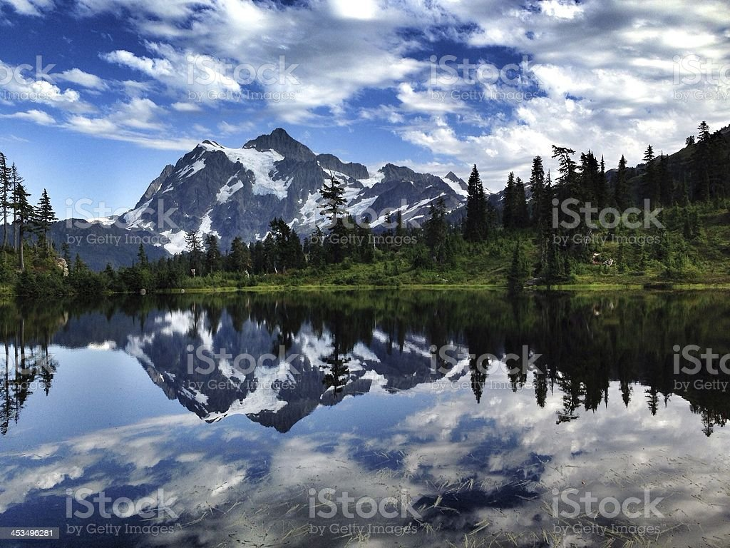 Mount Shuksan with blue sky and broken clouds stock photo