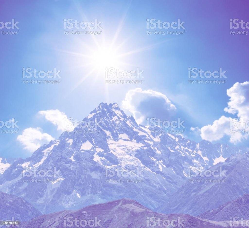 mount top in a snow under a sparkle sun, natural violer colorised background royalty-free stock photo