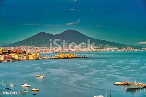 Beautiful sunset over the Bay of Naples with the Castel dell'Ovo in front of the famous Mt. Vesuvius. The Castel dell' Ovo is the oldest standing fortification in Naples.