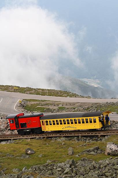 """Mount Washington Cog Railway """"Mount Washington, USA- July 8, 2011: A passenger train acends Mount Washington, New Hampshire. The Mount Washington Cog Railway started in 1869 and is the world\'s first such railway."""" mount washington new hampshire stock pictures, royalty-free photos & images"""