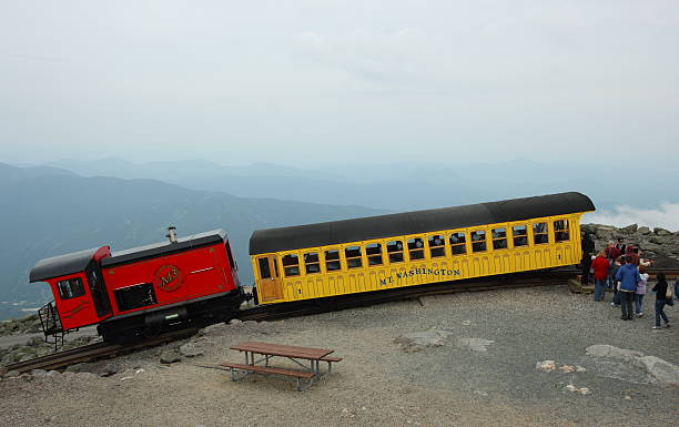 """Mount Washington Cog Railway Train """"Mount Washington, USA - JULY 8, 2011: Tourists board a train on Mount Washington, New Hampshire. The Mount Washington Cog Railway started in 1869 and is the world\'s first such railway."""" mount washington new hampshire stock pictures, royalty-free photos & images"""