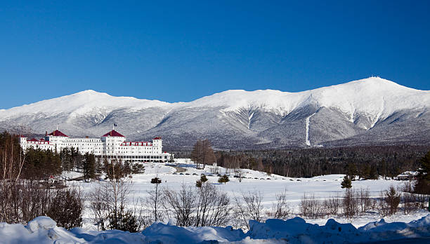 Mount Washington Scenic view of snow covered mountain and lodge at Mount Washington mount washington new hampshire stock pictures, royalty-free photos & images