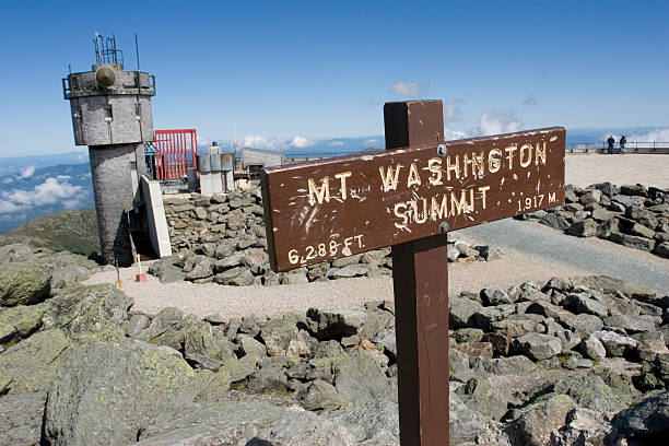 """Mount Washington (NH) Summit of Mt. Washington, New Hampshire. The highest peak east of the Mississippi and north of Virginia. The sign is weathered and beaten, as befits the famous """"worst weather"""" of the summit. The building in the background is the Mount Washington weather observatory and museum. mount washington new hampshire stock pictures, royalty-free photos & images"""