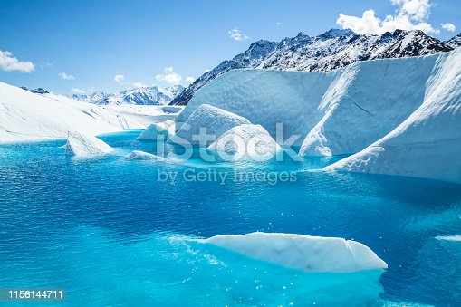 The summit of Mt Wickersham looming over the Matauska Glacier in Alaska. A crystal blue pool sits below the peak with fins of white ice sticking out of the blue waters.