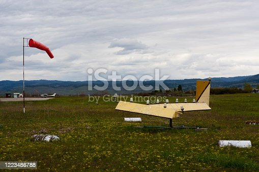 A windsock and wind vane at a small rural airport in the mountain town of Council, Idaho, USA with the mountains (and some snow) in the background.