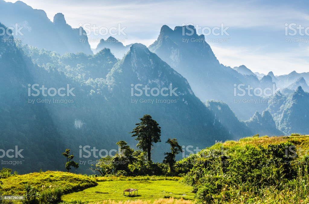 Mountain and blue sky at Kasi, Laos. and little home in grass field in front of mountain stock photo