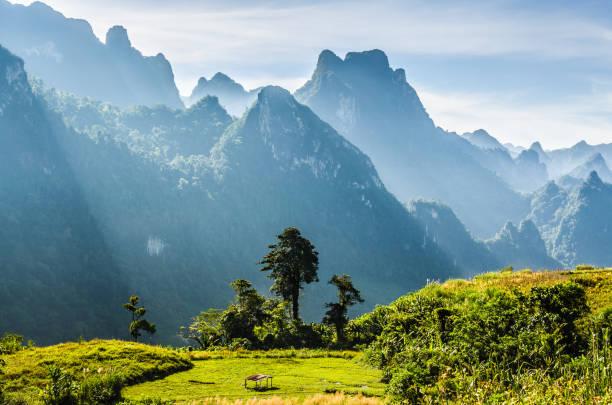 berg und blauer himmel an kasi, laos. und kleines zuhause in wiese vor berg - laos stock-fotos und bilder