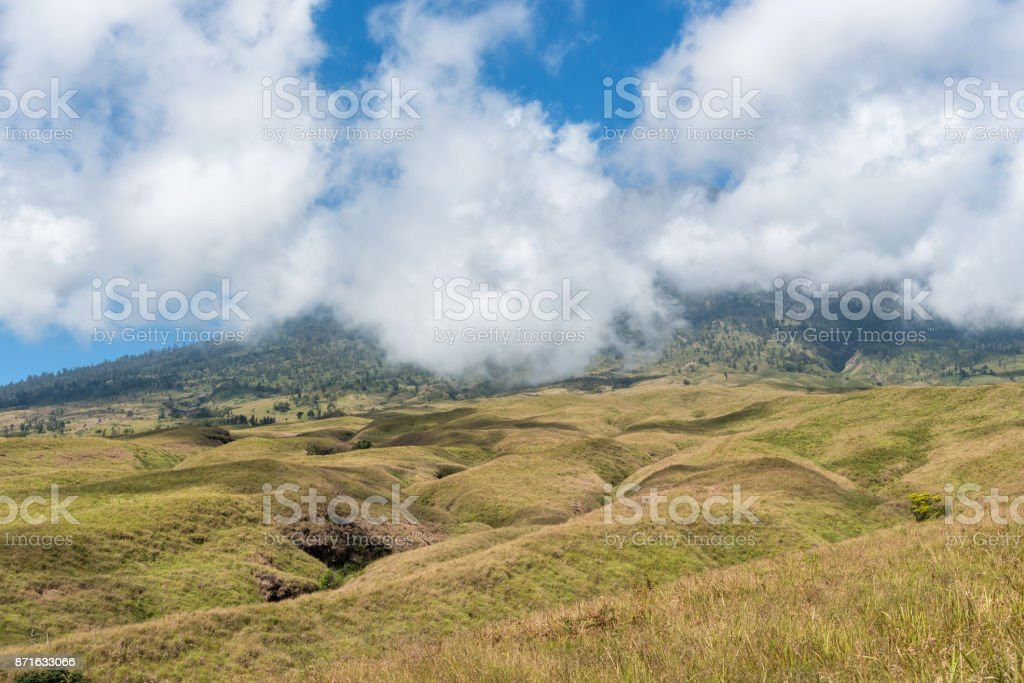 Mountain and savannah field with low cloud over hill. Rinjani mountain, Lombok island, Indonesia. stock photo