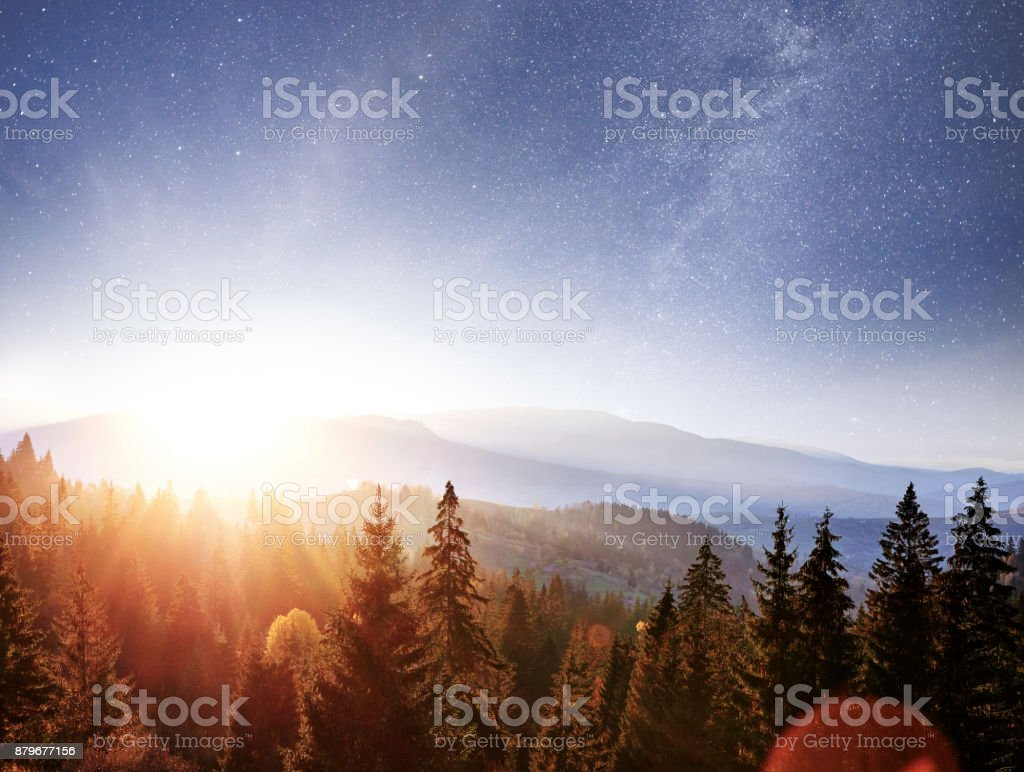 Mountain autumn landscape. High grass and vibrant night sky with stars and nebula and galaxy. Deep sky astrophoto stock photo