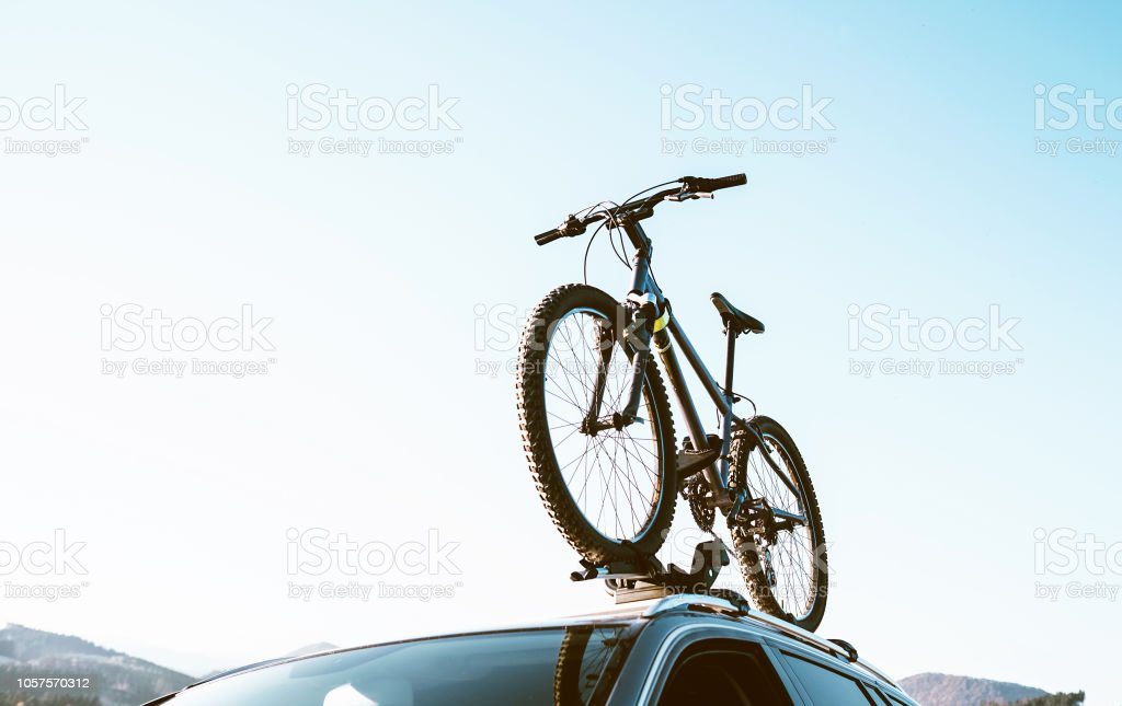 Mountain Bicycle fixed with Roof Mounted Bike Carriers instaled on white Auto roof travel concept image stock photo