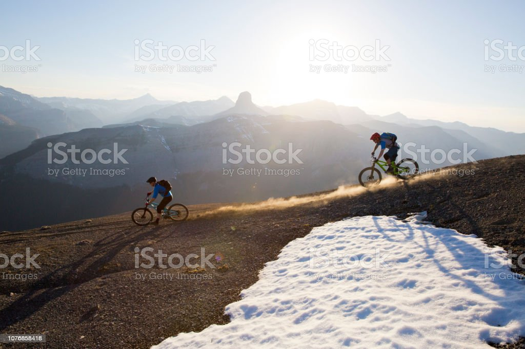 Two men ride their mountain bikes down a trail in the Rocky Mountains...