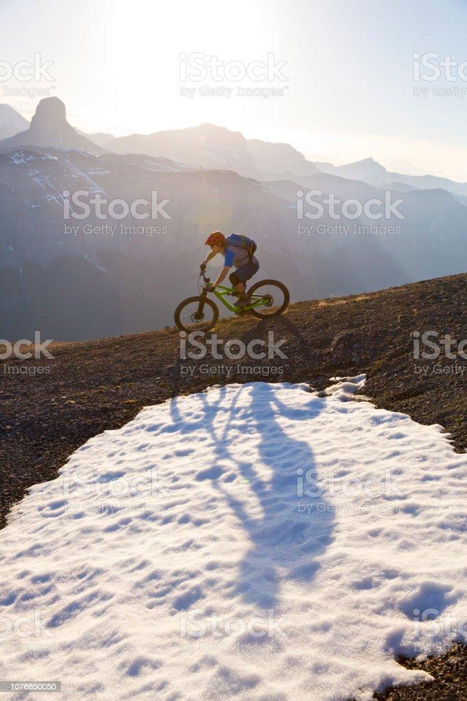 A man rides his mountain bike down a steep trail in the Rocky...