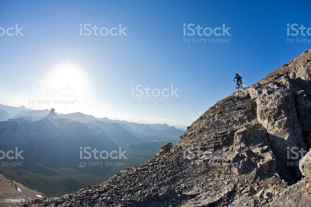 A male mountain bike rider goes down a steep and rough trail in the...