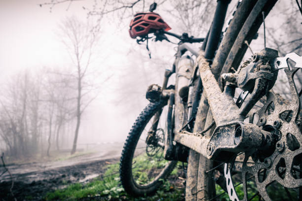 Mountain bike and helmet in autumn woods, dirty bicycle stock photo