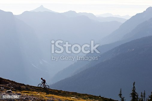 A male mountain bike rider rides up a single track trail in British Columbia, Canada.