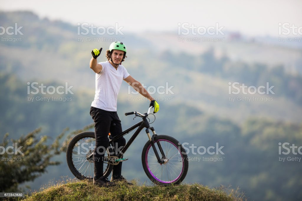 Mountain bike cyclist showing thumbs up on top of hill. stock photo