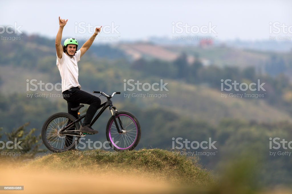 Mountain bike cyclist with arms raised on top of hill. stock photo
