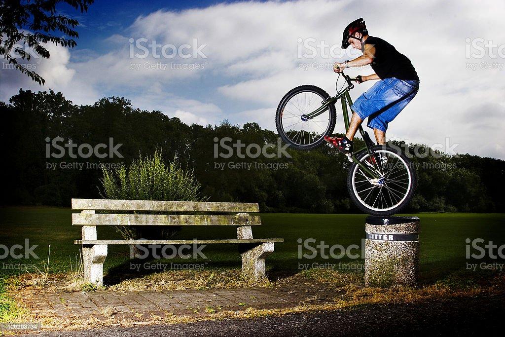 Mountain bike doing stunts onto bench stock photo