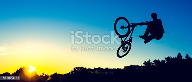 Shot of a mountain bike jump at sunset, copy space.