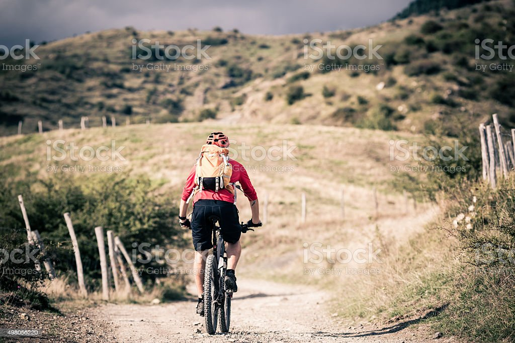 Mountain bike rider on country road, track trail in inspirationa stock photo
