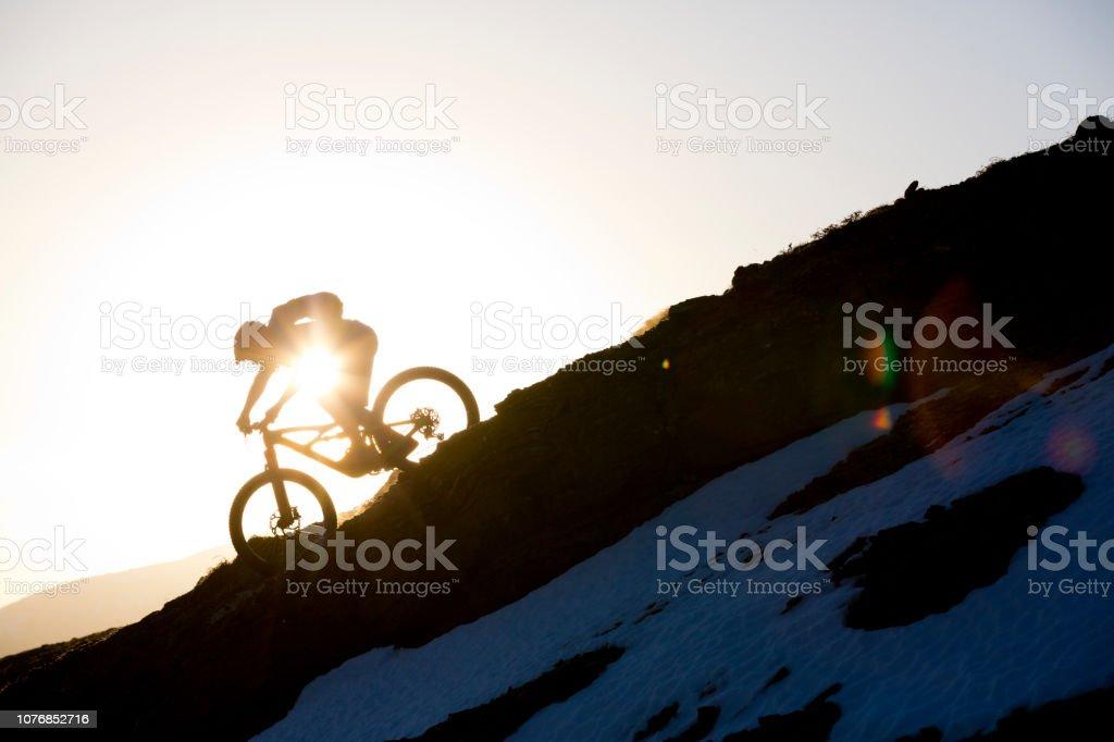 A male mountain bike rider goes down a steep trail as the sun goes...