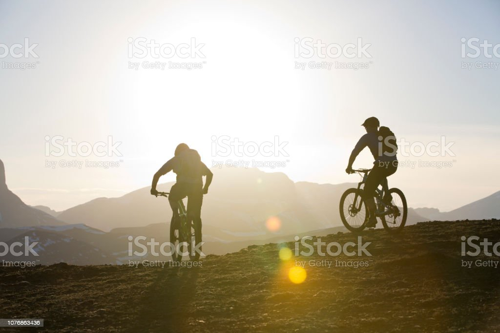 Two men ride their mountain bikes in the Rocky Mountains at the end...