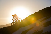 A male mountain biker rides a downhill trail at the end of the day.