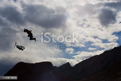 A male mountain bike rider flies through the air and is about to crash after hitting a big dirt jump.