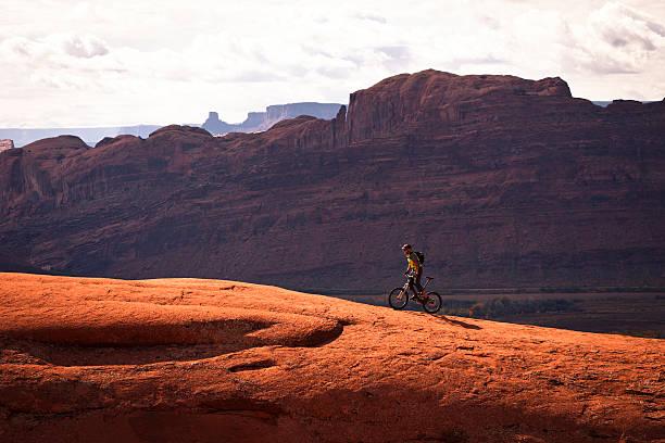 mountain biker climbing on slick rock. - moab utah stockfoto's en -beelden