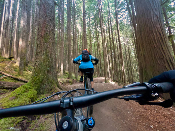POV of Mountain Biker Following Another on Cross Country Trail stock photo