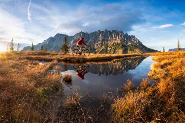 Mountain biker in front of mountain lake in the Alps - Mount Hochkönig stock photo