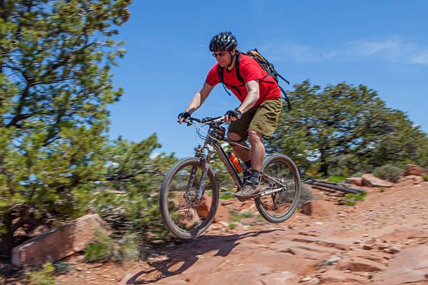 Mountain biker jumping rocks on a trail in Moab Utah. stock photo
