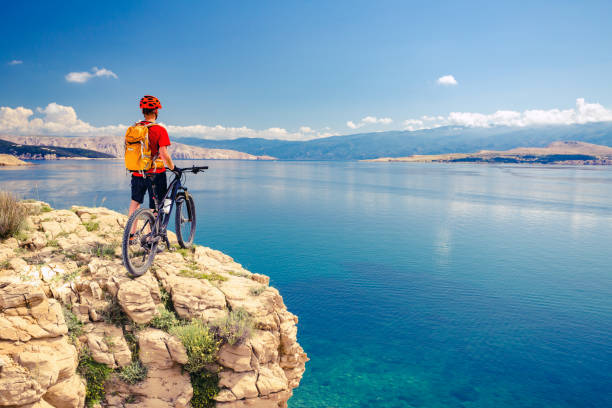 Mountain biker looking at view and riding a bike stock photo