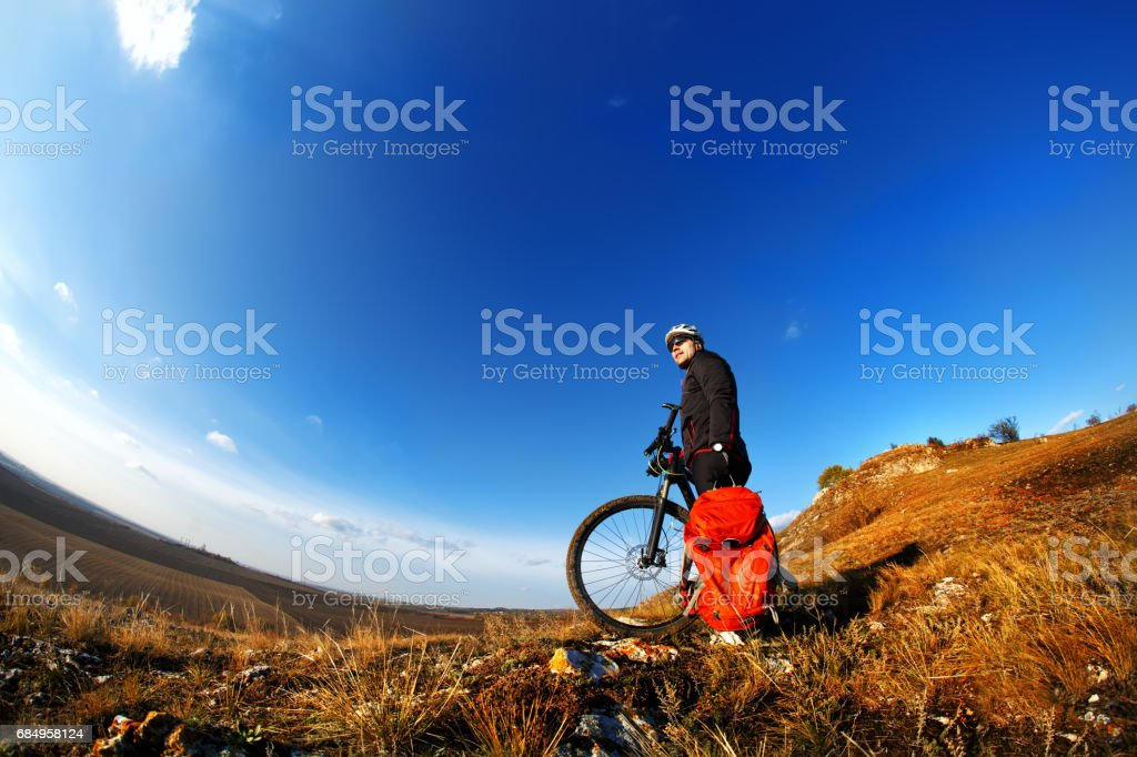 Mountain biker looking at view and traveling on bike with backpack. Lizenzfreies stock-foto