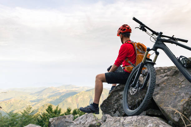 Mountain biker looking at view on bike trail in autumn mountains Mountain biker looking at inspiring landscape on bike rocky trail in autumn mountains. Riding on full suspension bike. Sport fitness, motivation and inspiration in beautiful inspirational landscape. mountain biking stock pictures, royalty-free photos & images
