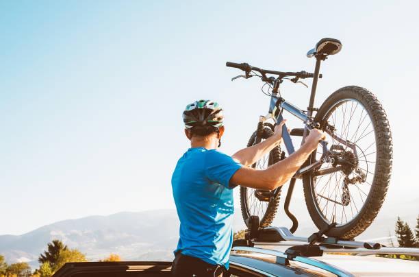 Motociclista hombre toma de su bicicleta desde el techo del coche - foto de stock
